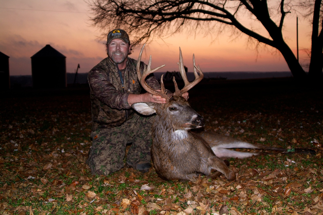 man holding up a dead deer's horns