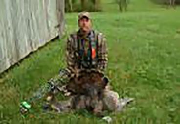 man kneeling with a dead turkey